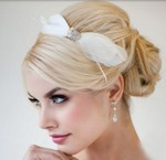 Blonde wedding hairstyle with low updo with feather hairclip and side band