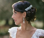 Bridal low updo hairstyle for winter wedding with beautiful crystal hairclip
