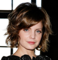 Medium short hairstyle with wavy layers and long side bang