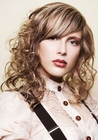 women curly hairstyle with layers and long swept bang and high lights.JPG